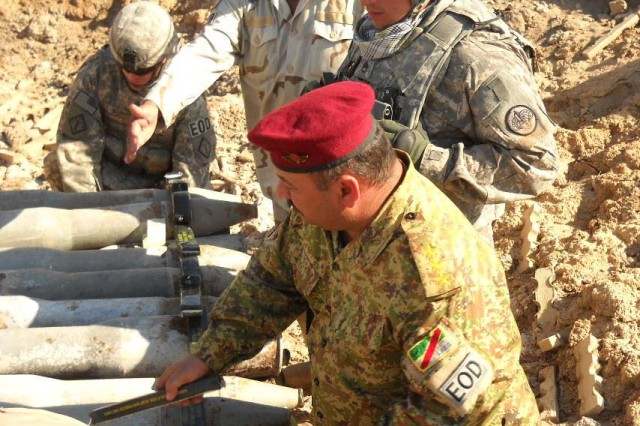 Capt. Imad Jassim, of the 8th Iraqi Army Bomb Disposal Company, prepares a cache of explosives for detonation at Joint Security Station Hamiyah.  Soldiers from the 3rd Armored Cavalry Regiment and 75th Explosive Ordnance Disposal Company assist with preparations prior to the live detonation and training event.