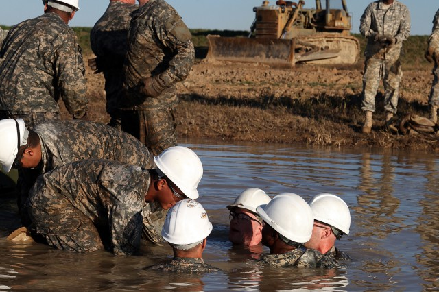 FORT LEE, Va. (Dec. 15, 2010) - Vehicle Recovery Students wade through the water to assess the situation of a M1 tank stuck in a muddy water pit during part of their training.