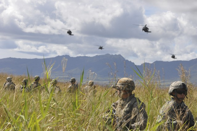 After assaulting an objective, Soldiers from A Troop, 3rd Squadron, 4th Cavalry Regiment, 3rd Brigade Combat Team, 25th Infantry Division, (foreground) pull security while waiting at East Range landing zone for UH-60 Black Hawk helicopters (background) from 25th General Support Aviation Battalion, 25th Combat Aviation Brigade, during an Air Assault training exercise at Wheeler Army Airfield, Nov. 30.  (Photo by Sgt. Karl Williams  25th Combat Aviation Brigade Public Affairs)
