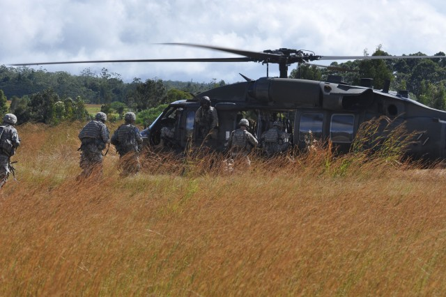 A UH-60 Black Hawk helicopter (background) from 25th General Support Aviation Battalion, 25th Combat Aviation Brigade, lands at East Range to picks up Soldiers from A Troop, 3rd Squadron, 4th Cavalry Regiment, 3rd Infantry Brigade Combat Team, 25th Infantry Division, after an Air Assault training exercise at Wheeler Army Airfield, Nov. 30.   (Photo by Sgt. Karl Williams  25th Combat Aviation Brigade Public Affairs)