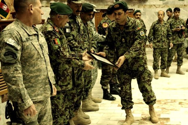 An Afghan National Army Bridmal Sergeants Major graduate receives his diploma from Afghan National Army Training Center Commander Maj. Gen. Aminullah Karim at Kabul Military Training Center, Dec. 14.