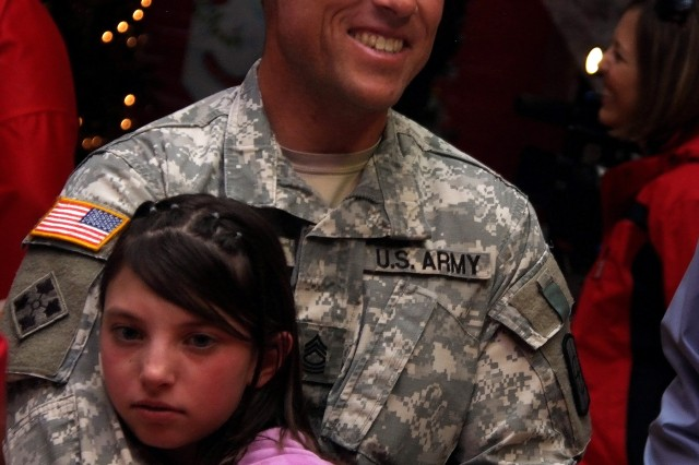 FORT CARSON, Colo. -- Master Sgt. Anthony Sours, 282nd Engineer Company, holds his daughter, Caitlin, while reuniting with Family and friends inside the Special Events Center at Fort Carson, Dec. 9.