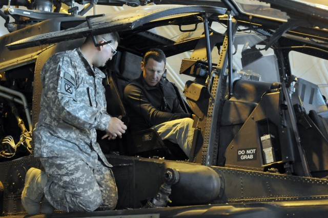 Sgt. Nelson Villamizar, an Apache armament avionic electrician of 6th Squadron, 6th Cavalry Regiment, 10th Mountain Division, shows Lance Armstrong how the AH-64 Apache operates during his Dec. 15, USO tour at Forward Operating Base Fenty, in eastern Afghanistan's Nangarhar Province.