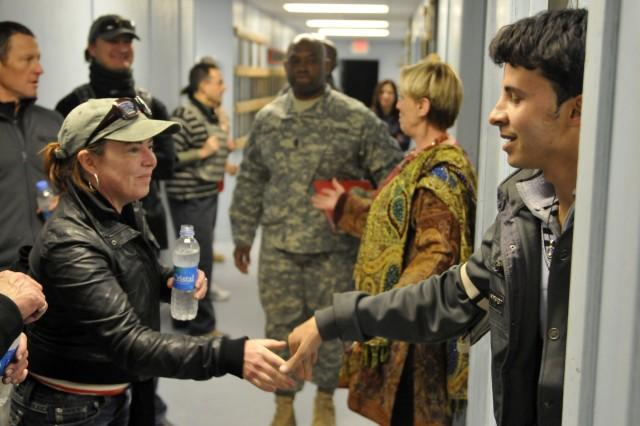 Comedian Kathleen Madigan greets Muhammad Tamim Samadi, U.S. Department of State translator, while visiting several offices during a USO tour at Forward Operating Base Fenty, near Jalalabad, Afghanistan, Dec. 15.