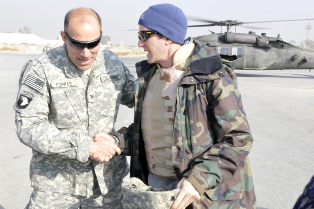 Col. Andrew P. Poppas, Task Force Bastogne commander, greets Lance Armstrong upon arrival to Forward Operating Base Fenty, in eastern AfghanistanAca,!a,,cs Nangarhar province, Dec. 15.