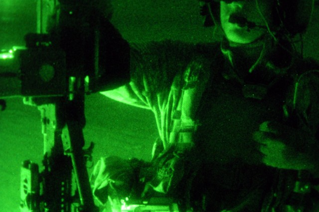 Spc. Corey Corr, an Army Black Hawk helicopter crew chief, holds a machine gun mounted to the side of his aircraft before a mission in the Baghdad area, Dec. 10. Corr is assigned to the 3rd Assault Helicopter Battalion, 1st Aviation Regiment.