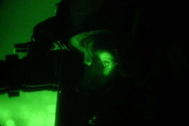 Sgt. 1st Class Wilford Goeller, an Army Black Hawk helicopter crew chief, scans the Iraqi countryside with night vision goggles during a mission in the Baghdad area, Dec. 10. Goeller is assigned to the 3rd Assault Helicopter Battalion, 1st Aviation Regiment.