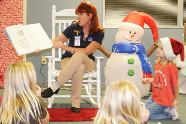 Tammy Sanders, Picerne Military Housing relocation specialist, reads a Christmas story to a group of children during Picerne's annual Milk and Cookies with Santa at the Rucker-Picerne Partners Building Dec. 9.