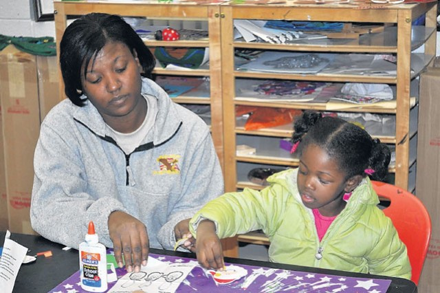 Sanaa Mabery, 4, makes a Santa ornament with her mother, Sgt. Cantress Noel-Mabery at Youth Services Friday.