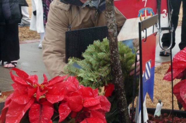 Staff Sergeant William Bowman, Net-Centric Operating Environment, Fort Benning, places a wreath at the memorial tree dedicated to his fallen comrade, Sgt. Gene L. Lamie, following the 4th Annual Wreaths for Warriors Walk wreath ceremony at Fort Stewart's Cottrell Field, Dec. 11.