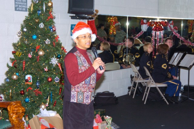 "Col. Marilyn D. Brew, Deputy Surgeon, JFHQ NCR/MDW, stands beside members of the United States Army Band ""Pershing's Own"" as she welcomes staff members to the 2010 command Holiday Social at Fort McNair's gym 16 Dec., 2010.  Santa made an appearance and presented gifts to a number of employees.  Also, a traditional holiday spread featuring turkey, ham, stuffing and various types of deserts were served to staff members along with soft drinks and eggnog."