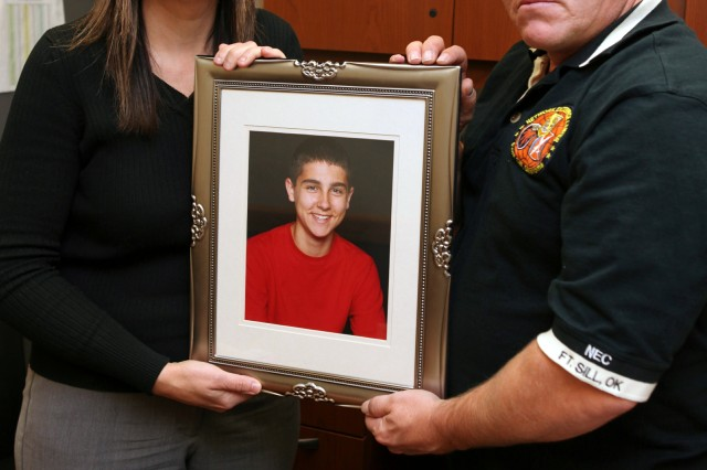 Michelle and David Rauls hold a photograph of their son Nicholas, 13, on Dec. 1 at Knox Hall. Nick committed suicide Feb. 7, 2010, at the family's Elgin home. Since his death, the Rauls have been involved in suicide prevention awareness. Michelle works as an administrative assistant at G/3 Current Operations and David is a video teleconference coordinator at the Fort Sill Network Enterprise Center.
