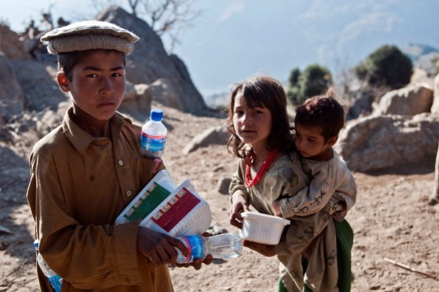 An Afghan girl carrying her baby brother clutches a box of food while her older brother stands by at a small village outcropping on a mountainside overlooking the Pech River Valley in eastern Afghanistan's Kunar Province Nov. 23. Soldiers from Company B, 1st Battalion, 327th Infantry Regiment, Task Force Bulldog, 1st Brigade Combat Team, 101st Airborne Division, cleared this village during Operation Bulldog Bite and handed out some food to this girl and her siblings.