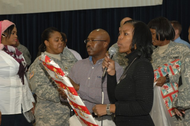 W.A. Fountain Elementary School Principal Jamilah Hud-Kirk announces the names of fourth and fifth grade students as George Benjamin, First Army Operations Division, helps to distribute gifts to each of the more than 600 students here Dec. 17.