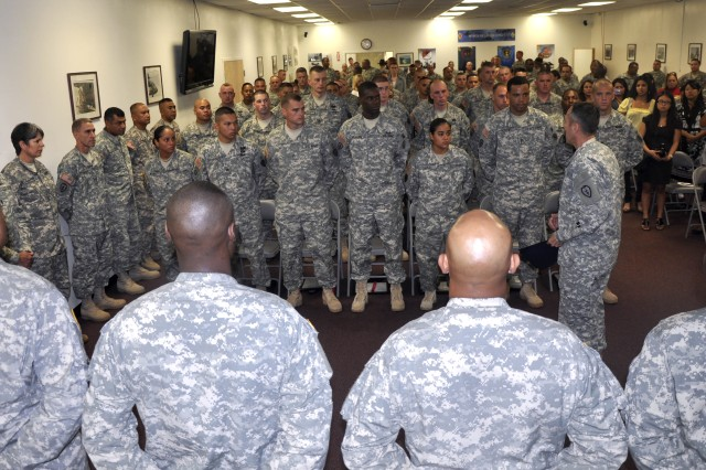Command Sgt. Maj. Jesus Ruiz (standing, center), brigade command sergeant major, 25th Combat Aviation Brigade (CAB), addresses the Wheeled Vehicle Mechanic Advanced Leaders Course Class #702-11 instructors, graduates and family members, after their graduation, in 25th CAB's Multi-Purpose Room of Excellence on Wheeler Army Airfield, Dec 14.  (Photo by Sgt. Karl Williams  25th Combat Aviation Brigade Public Affairs)