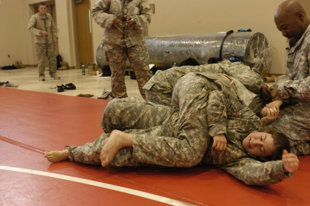 CORAOPOLIS, PA - Staff Sgt. Jessica Miller, platoon sergeant, 326th Quartermaster Company, New Castle, Pa., takes part in combatives training conducted at the 316th Expeditionary Sustainment Command held here.  The training was conducted Dec. 13 through Dec. 17.  Combatives focuses on hand-to-hand techniques and requires Soldiers to utilize strength, flexibility and endurance movements.   (U.S. Army photo by Staff Sgt. Amber Greenlee, 316th ESC Headquarters' Public Affairs Office.)