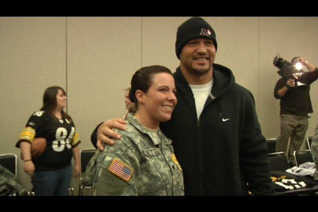 "PITTSBURGH, PA -- Pittsburgh Steelers' Inside Linebacker James Farrior talks with Spc. Crystal Whetzel, 14th Quartermaster Company, as she participates in a video gaming event with deployed Soldiers and other members of the Steelers organization.  Steelers players competed with the military personnel attending, while deployed Soldiers in Iraq and Afghanistan participated via satellite. This event was sponsored by the nonprofit organization ""Pro vs. GI Joe"" which partners with the NFL and NBA teams throughout the country to facilitate gaming competitions among military members and pro athletes. (U.S. Army photo by Sgt. Stephen Crofoot, 316th ESC Headquarters' Public Affairs Office.)"