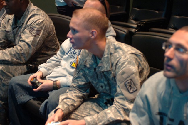 "PHILADELPHIA , Pa.- Army Reserve Soldiers and local Airmen compete with one another on the big screen in a video game competition held here at the Eagles Training Facility. NFL players competed with the military personnel attending, while deployed Soldiers in Iraq and Afghanistan participated via satellite. This event was sponsored by the nonprofit organization ""Pro vs. G.I. Joe"" which partners with the NFL and NBA teams throughout the country to facilitate gaming competitions among military members and pro athletes. Over 75 uniformed military personnel participated. Army Reserve Soldiers from the 316th Expeditionary Sustainment Command along with local Airmen, Marines and National Guardsmen took part. (U.S Army Photo by Army Maj. Kevin McNamara, 316th Expeditionary Sustainment Command Headquarters' Public Affairs Office)"