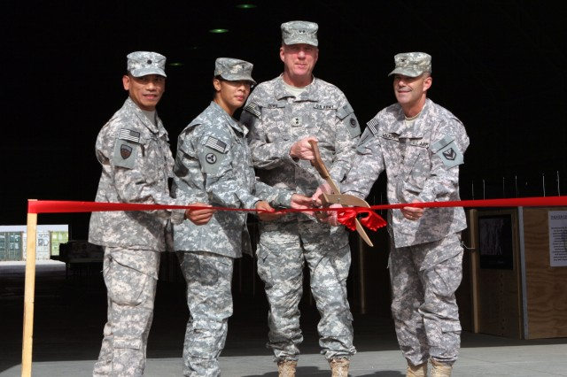 Leaders_smil_cut: Maj. Gen. Kenneth S. Dowd (third from left), commanding general of the 1st Theater Sustainment Command, joins leaders with the 1st Sustainment Brigade and the 469th Combat Sustainment Support Battalion in a ribbon cutting, Dec. 17, to mark the opening of the Camp Buehring, Kuwait Central Issue Facility. Personnel deploying into the Central Command area can now get and turn in their military gear at this CIF in Kuwait, thereby eliminating the need to lug heavy duffle bags on planes, through airports, and through customs.