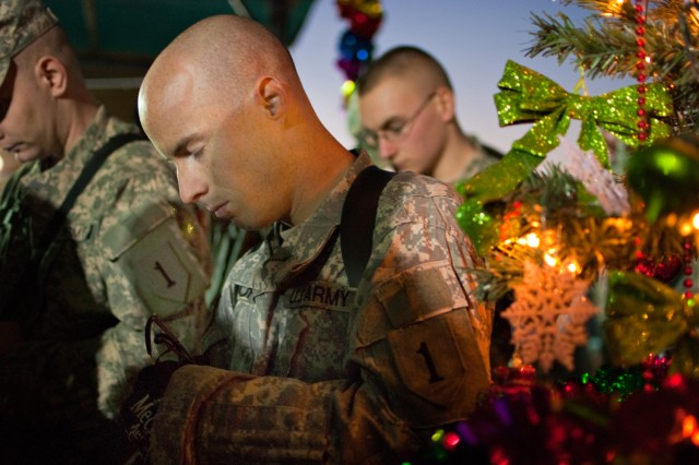 Staff Sgt. Joshua Horst, 29, of Port Richey, Fla., lowers his head in prayer during a holiday party put on by his unit on Camp Taji, Iraq, Dec. 19. Horst, an Apache attack helicopter mechanic, is spending his third Christmas in Iraq. (U.S. Army photo by Spc. Roland Hale, eCAB, 1st Inf. Div. PAO)