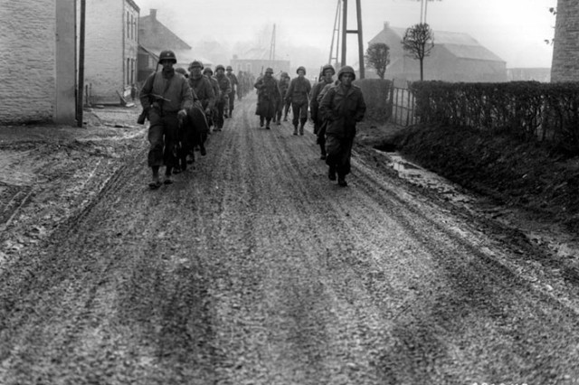 U.S. troops of the 28th Infantry Division, who have been regrouped in security platoons for defense of Bastogne, Belgium, march down a street.  Some of these Soldiers lost their weapons during the German advance in this area.  Bastogne, Belgium Dec. 20, 1944.