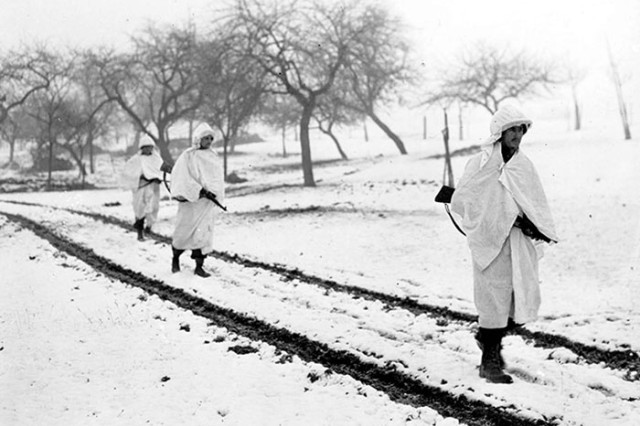 Three members of an American patrol cross a snow covered field at Lellig, Luxembourg on a scouting mission, Dec. 30, 1944.  White bedsheets camouflage them in the snow.  Left to right:  Sgt. James Storey, Newmand, Ga.; Pvt. Frank A. Fox, Wilmington, Del., and Cpl. Dennis Lavanoha, Harrisville, N.Y.