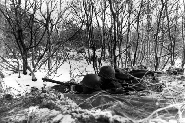 An American road-block is set up with 30 caliber heavy machine gun, and a tank destroyer is ready for action on Adolph Hitler Strasse.  1st Battalion, 157th Regiment, 45th Division, Dec. 10, 1944.