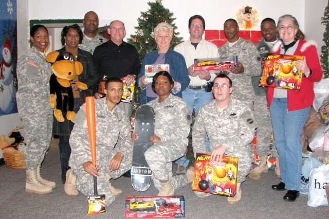 Soldiers and members of ProCare RX, Atlanta, pose with toys donated to Operation Gift Dec. 10 after the company donated more than $5,000 worth of gifts to the cause. ProCare RX, founded by Roger Burgess, a Vietnam veteran, and his wife, Barbara, has contributed to Operation Gift, which helps Soldiers with financial need have a better Christmas, for the past four years.