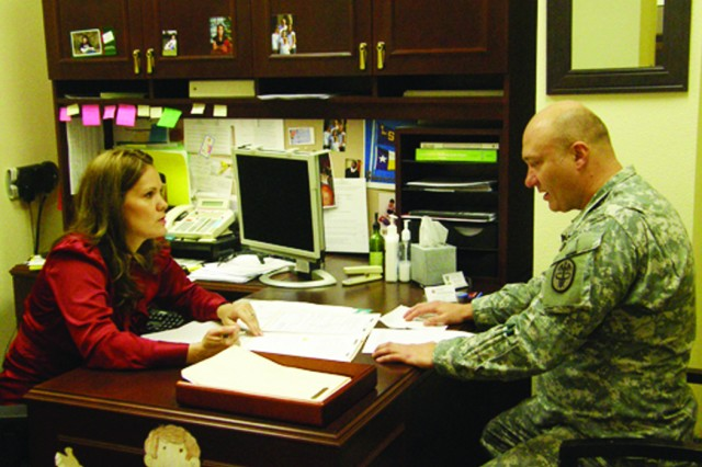 Melissa Baesler, Warrior Transition Unit nurse case manager, and 1st Lt. William Harvey, WTU nurse case manager, go over schedules and appointments for some of their WTU Soldiers.
