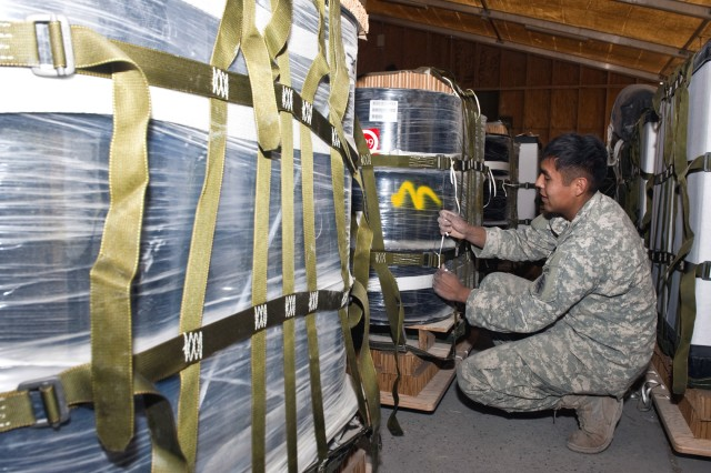 Spc. Nolan R. Barbone, rigger, Special Operations Task Force - South, prepares fuel drums for an aerial resupply Dec. 14, at Kandahar Airfield, Afghanistan.