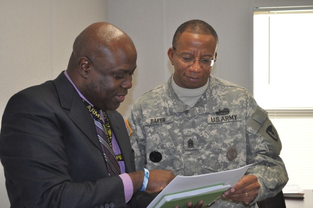 "Command Sgt. Maj. Tony L. Baker, Army Contracting Command command sergeant major, reviews a training status report with Keith Jackson, ACC deputy G3.  Baker is the first of ACC's senior leadership team to report for duty at the command's forward headquarters at Redstone Arsenal, Ala., as part of Headquarters ACC's move from Fort Belvoir, Va.  ""I'm excited to be one of the ACC pioneers as we move our headquarters to Redstone,"" Baker said."