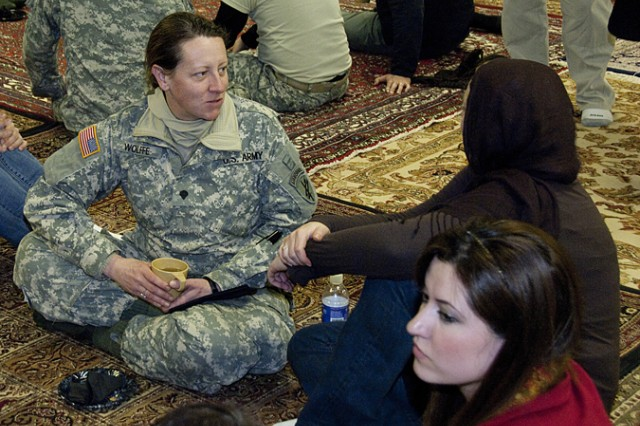 Spc. Marya Wolffe, of Wisconsin's 432nd Reserve Civil Affairs Battalion, speaks with a female Afghan role player during the traditional Afghan dinner held during joint civilian-military training at Muscatatuck Urban Training Center, Indiana, Dec. 16.