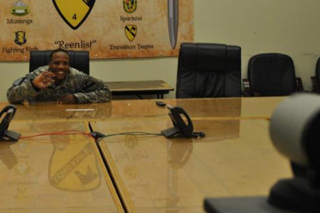 Spc. Andres Montero, training room non-commissioned officer for  A Company,  27th Brigade Support Battalion, 4th Advise and Assist Brigade, 1st Cavalry Division,  waves to his Family during the video teleconference set up by Meadows Elementary School at Fort Hood, Texas Dec. 14.