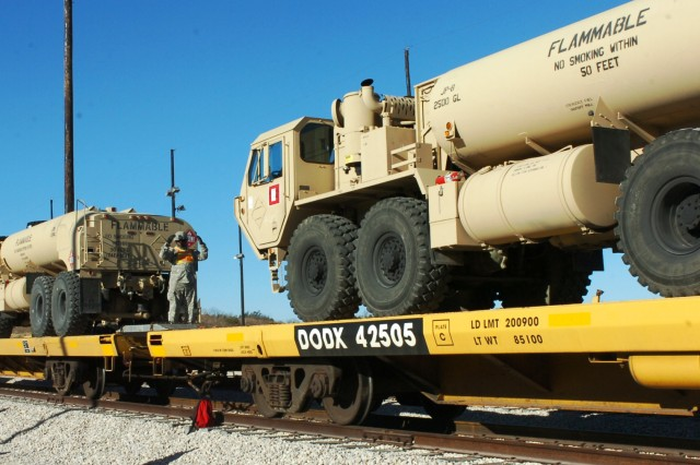 FORT HOOD, Texas- Sgt. Derrell Springer, a Brooklyn, N.Y. native and surveyor for Headquarters and Headquarters Battery, 3rd Battalion, 82nd Field Artillery Regiment, 2nd Brigade Combat Team, 1st Cavalry Division, ground-guides a fuel truck onto a flatbed train car during the 2nd BCT's railhead operations on Fort Hood, Texas Dec. 13.