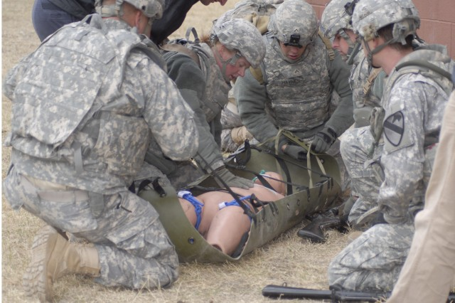 FORT HOOD, Texas - 3rd Brigade Combat Team, 1st Cavalry Division Soldiers look over a casualty to make sure he is stable.