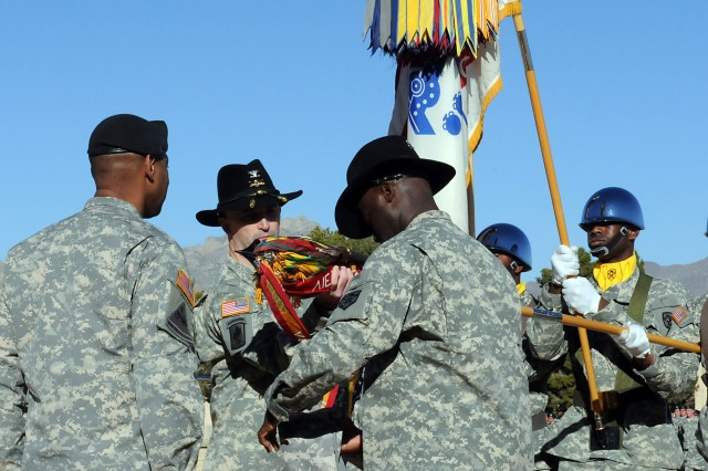 """Maj. Gen. Dana J.H. Pittard, Fort Bliss commanding general stands at attention while Col. James Ryan (Middle), commander, 15th Sustainment Brigade and Command Sgt. Maj. Nathaniel Bartee Sr., the brigade's sergeant major, uncases the brigade's colors during an Uncasing Ceremony on Noel Field here Dec 8 which officially established the """"Wagonmasters"""" as members of Team Bliss. (U.S. Army Photo by Cpl. Jessica Hampton, 15th Sustainment Brigade Public Affairs)"""