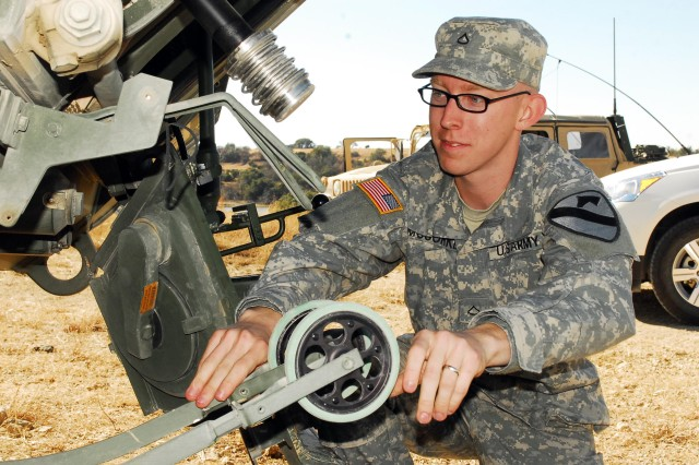 Pfc. Matthew McCorkle, a chemical operations specialist with 2nd Special Troops Battalion, 2nd Brigade Combat Team, 1st Cavalry Division, examines a double-wheel sampling system on a Stryker Nuclear, Biological, Chemical Reconnaissance vehicle during field training on Fort Hood, Texas, Dec. 15.