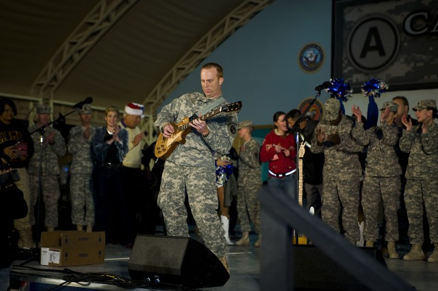 "Staff Sgt. Chad B. Leader, lead guitarist for the Army Band ""Downrange,"" plays America the Beautiful during the Sergeant Major of the Army Hope and Freedom Tour at Camp Arifjan, Kuwait, Dec. 17. Sgt. Maj. of the Army Kenneth O. Preston and several entertainers are touring various countries in partnership with the USO, visiting deployed servicemembers throughout the Central Command's area of responsibility this holiday season."