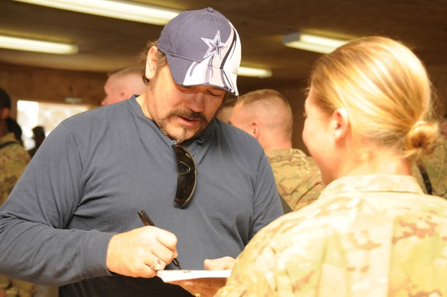 LOGAR PROVINCE, Afghanistan - Country Music singer Buddy Jewell of Nashville, Tenn., signs autographs for Soldiers of 94th Brigade Support Battalion's Task Force Strength, 4th Brigade Combat Team, 10th Mountain Division, during a USO visit to Forward Operating Base Shank Dec. 21. (Photo by U.S. Army Spc. Brian P. Glass, Task Force Patriot Public Affairs)