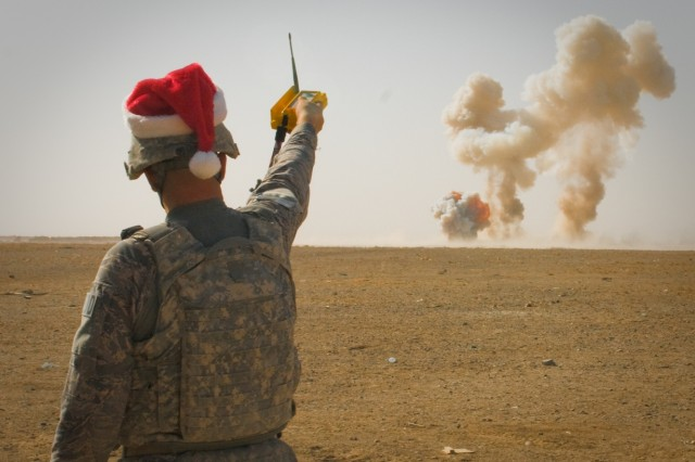 101222-A-5634G-001: U.S. Air Force Tech.  Sgt. Robert L. Woods, 466th Air Expeditionary Group, Explosive Ordnance Disposal team leader, detonates home-made explosives and expired ammunition while dressed in a Santa hat Dec. 22, outside Kandahar Airfield, Afghanistan. His home unit is the 123rd Airlift Wing in Louisville, Kentucky. (U.S. Army photo by Spc. Edward A. Garibay, 16th Mobile Public Affairs Detachment)
