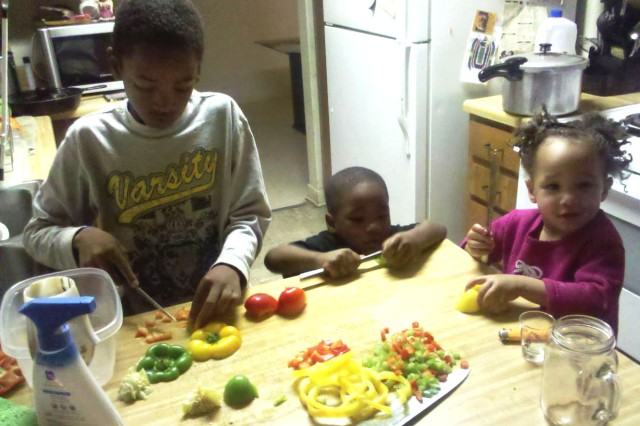 Ten-year-old Donnie III, 4-year-old Dayon and 2-year-old Seagurin help prepare dinner. Their father, Donnie Mock, has a big holiday dinner planned to help keep spirits high while his wife, Army Sgt. Kelly Mock, is deployed in Afghanistan.