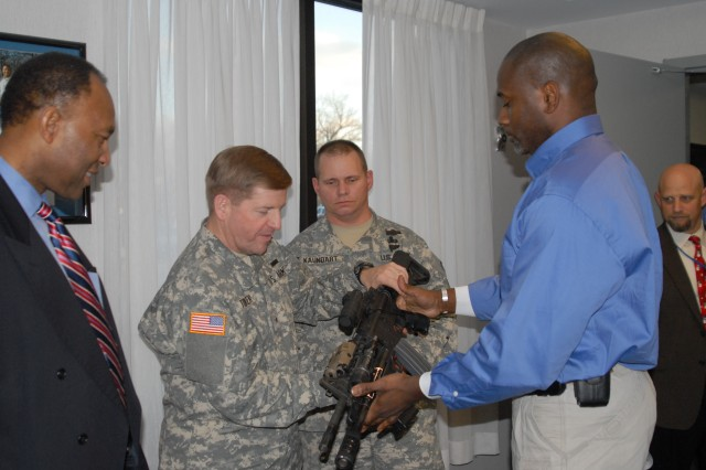 Brig. Gen. Christopher Tucker gets his hands on the latest in weapon technology during his Dec. 20 tour of PEO Soldier.