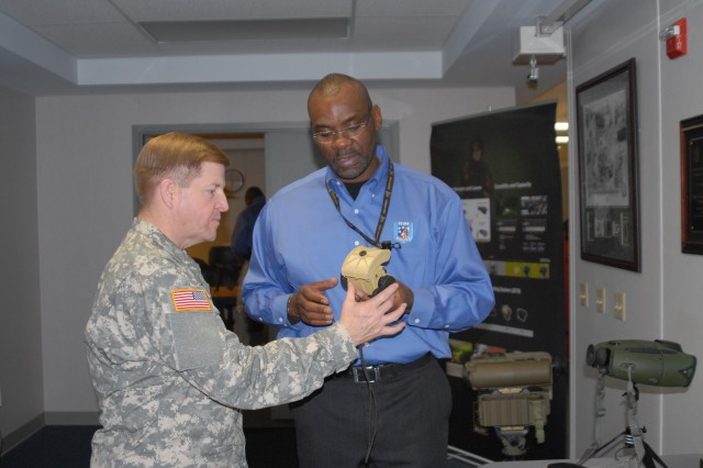 A PEO Soldier representative explains a piece of equipment to Brig. Gen. Christopher Tucker during his visit Dec. 20.