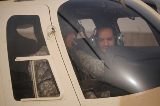 Army Chief Warrant Officer Jason Glenn, experimental test pilot, Redstone Test Center, Ala., shows an Iraqi pilot the different controls on the T407 before test flying the aircraft, recently, during a partnership day in Iraq. The training helicopters will help train qualified Iraqi army pilots to operate and maintain the Iraqi Armed 407 Armed Scout Helicopters which are scheduled to be fielded by the end of 2011.