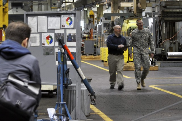 Media Stream cameraman positions boom as Col. Mark F. Migaleddi and Arsenal employee, Bill Dingmon, walk along machinery during filming.