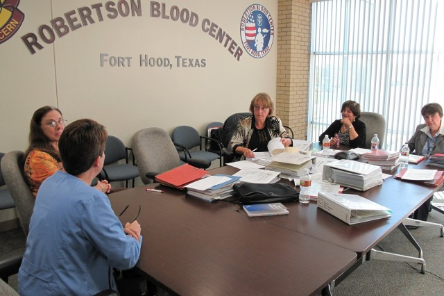 Cheryl Austin and Elaine Perry of the Robertson Blood Center, and Jill Hoag, Dr. Geeta Paranjape, and Mary Barrera of the AABB examine records at the Robertson Blood Center at Fort Hood, Texas on Nov. 2, 2010.
