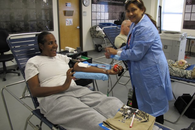 Spc Raysa Rondon donates blood with Merledic Casado at an Armed Services Blood Drive at the Warrior Transition Unit at Fort Hood, Texas on October