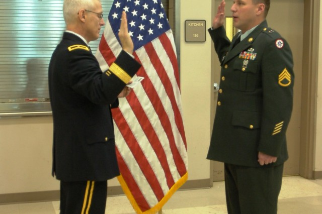 CORAOPOLIS , Pa. - Brig. Gen. Peter S. Lennon, Commander, 316th Expeditionary Sustainment Command, recites the Oath of Enlistment while Staff Sgt. Frederick Holt repeats each line as he re-enlists here Dec. 18 during Family Day. Holt is the supply sergeant for Headquarters and Headquarters Company, 316th ESC. Holt, from Oakdale, Pa., has spent the last 13 years on active duty with the US Army.