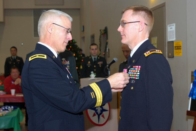 CORAOPOLIS, Pa. -- Brig. Gen. Peter S. Lennon, Com-mander, 316th Expeditionary Sustainment Command, pins Capt. Paul Sutton of Verona, Pa., with a Meritori-ous Service Medal during Family Day here Dec. 18. Family Day was a combination holiday celebration and awards presentation for Soldiers of the 316th ESC. Sutton, a 316th ESC Solider, retired this year after twenty-two years of service with both the Active Army and the Army Reserve.