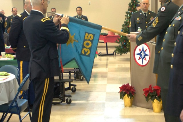 CORAOPOLIS, Pa. -- Brig. Gen. Peter S. Lennon, Com-mander, 316th Expeditionary Sustainment Command, at-taches a streamer to the unit flag of the 305th Military History Detachment in recognition of the Meritorious Unit Citation during Family Day here Dec. 18. Family Day was a combina-tion holiday celebration and awards presentation for Soldiers of the 316th ESC. The 305th MHD is a subordinate unit of the 316th ESC which has deployed to multiple combat zones. The 305th MHD also received the Reserve Officer Associa-tion Outstanding U.S. Army Reserve Small Unit Award to rec-ognize their outstanding service throughout the years. The unit was also recognized for their deployment to Afghanistan from 2006 thru 2008. The unit is being recognized for pro-ducing the first historical documentation of Operation Endur-ing Freedom.
